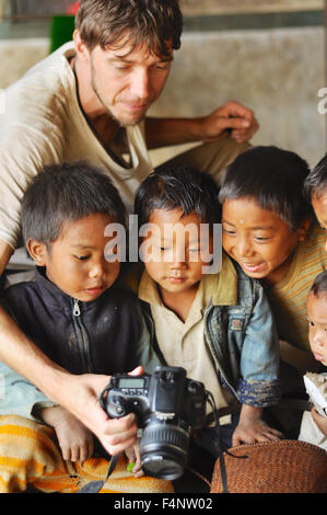 Nagaland, India - March 2012: Young photographer shows pictures on digital camera to small boys in village in Nagaland, - Stock Photo