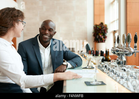 Happy young man sitting with woman at bar counter. Business couple at cafe after work. - Stock Photo