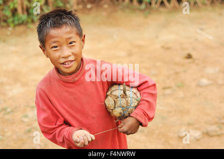 Nagaland, India - March 2012: Small boy with self-made ball plays football in Nagaland, remote region of India. - Stock Photo