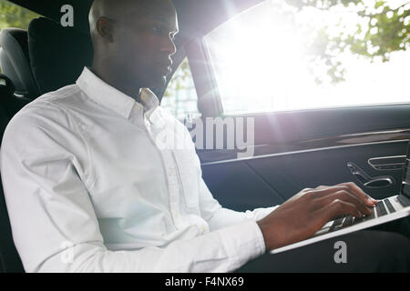Businessman traveling to office in the luxury car on the back seat and working on the laptop. - Stock Photo