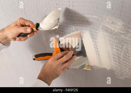manual worker with wall plastering tools inside a house - Stock Photo