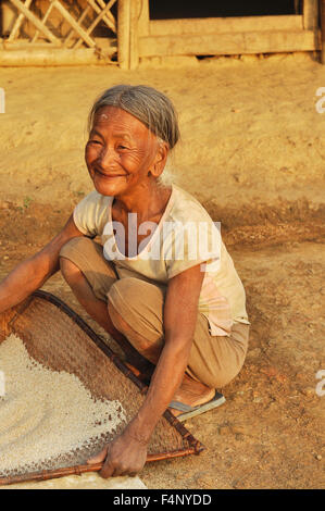 Nagaland, India - March 2012: Happy old woman sifts flour in Nagaland, remote region of India. Documentary editorial. - Stock Photo