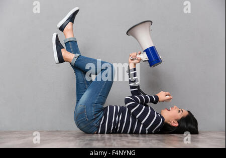 Young beautiful happy smiling woman lying with legs up and speaking in megaphone - Stock Photo