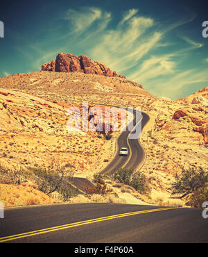 Retro toned winding desert highway, travel adventure concept, Valley of Fire State Park, Nevada, USA. - Stock Photo