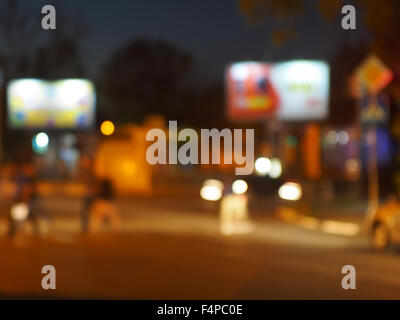 Abstract urban night scene with blurred headlights on the road. Blur and defocused lights from the headlights of - Stock Photo