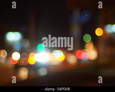 Abstract blurred image of lights and flare from the headlights of cars on a city street at night to use as a background. - Stock Photo