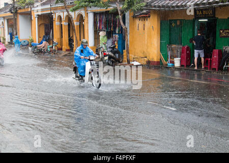 Hoi An ancient town Vietnam, biker on scooter motorcycle rides through flooded road during thunderstorms,Vietnam Stock Photo