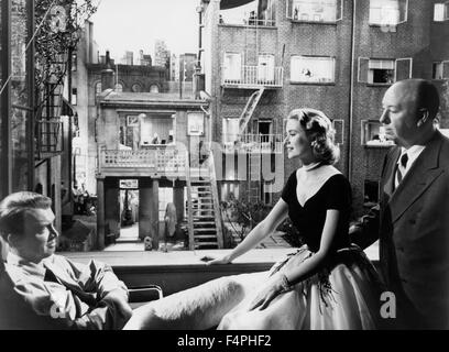 On the set, Grace Kelly between James Stewart and Alfred Hitchcock / Rear Window / 1954 directed by Alfred Hitchcock - Stock Photo