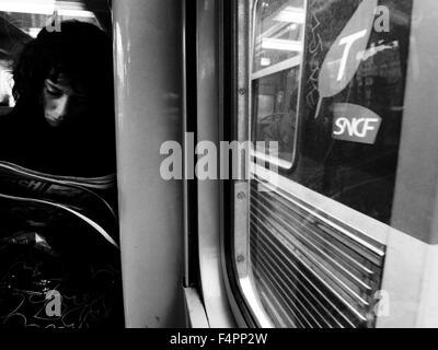 AJAXNETPHOTO. PARIS, FRANCE. - TRAIN TRAVEL - A PASSENGER ON A FRENCH COMMUTER TRAIN READING. PHOTO:JONATHAN EASTLAND/AJAX - Stock Photo