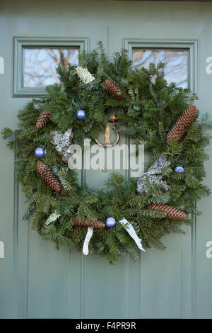 A Christmas wreath decorated with birch bark, lichen, pine cones, and glass balls hangs on a door in the Berkshires. - Stock Photo