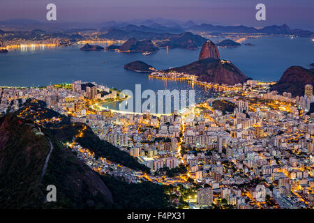 Spectacular aerial view over Rio de Janeiro as viewed from Corcovado. The famous Sugar Loaf mountain sticks out - Stock Photo