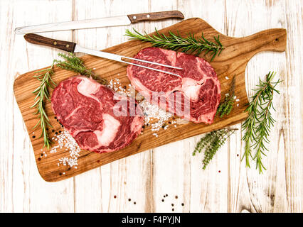Fresh raw meat Ribeye Steak with herbs and spices on wooden desk. Food background - Stock Photo