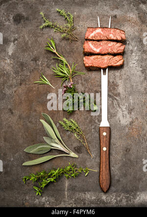 Grilled beef meat  with herbs and spices on metal kitchen desk. Food background - Stock Photo