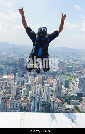 Kuala Lumpur, Malaysia-October 09, 2010: A BASE jumpers in jumps off from Kuala Lumpur Tower. KL Tower BASE Jump - Stock Photo