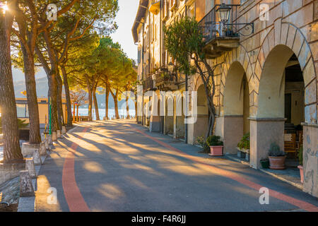 Street with sunlight and old buildings on the waterfront with trees in Morcote, Ticino - Switzerland. - Stock Photo