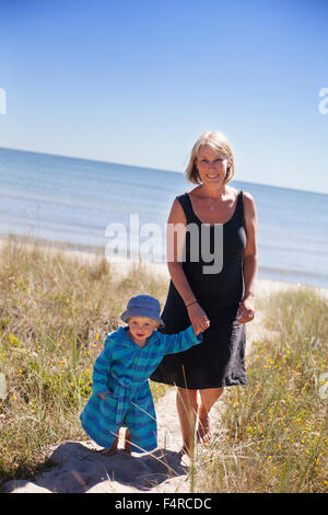 Sweden, Gotland, Faro, Skalasand, Mother and son (2-3) walking along beach footpath - Stock Photo