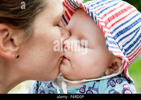 Woman kissing her baby daughter (6-11 months) - Stock Photo