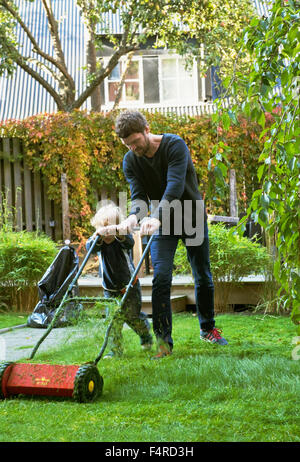 Sweden, Skane, Osterlen, Borrby, Father and son (4-5) mowing lawn in domestic garden - Stock Photo