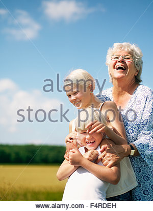 Outdoor portrait of grandmother with two granddaughters (6-7, 12-13) - Stock Photo
