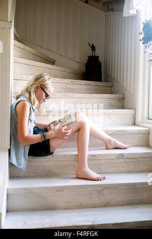 Sweden, Skane, Vejbystrand, Girl (10-11) reading book on wooden steps at home - Stock Photo