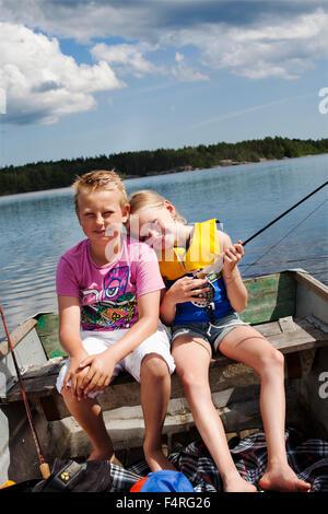 Girl and boy (8-9, 10-11) fishing on lake - Stock Photo