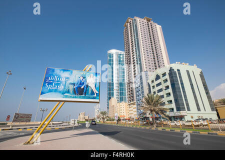 View of street and high-rise modern buildings on Corniche street in Ajman emirate in United Arab Emirates - Stock Photo