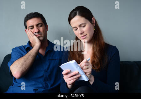 Worried couple listing expenses in the living room. Money and relationship  concept - Stock Photo
