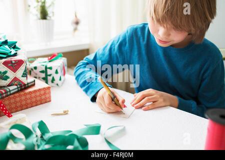 Boy (10-11) writing Christmas cards - Stock Photo