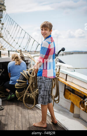 Germany, Mecklenburg-Vorpommern, Rugen, Portrait of teenage boy (14-15) on boat deck - Stock Photo