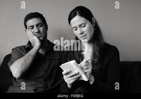 Worried couple listing expenses in the living room. Money and relationship  concept (BW) - Stock Photo