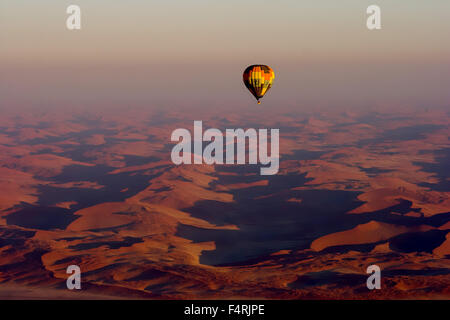 Breathtaking View. Hot Air Balloon flying over Red Sand Dunes, Namibia. - Stock Photo