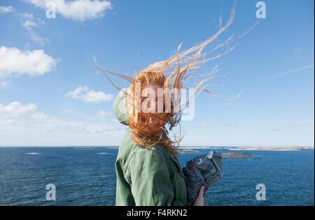Sweden, Swedish West Coast, Bohuslan, Skaftolandet, Young woman standing at seaside - Stock Photo