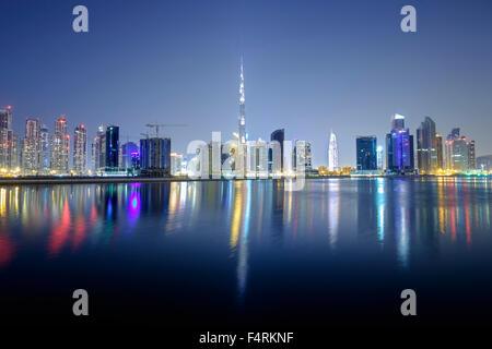Night view of Burj Khalifa and Creek at new Business Bay district of  Dubai United Arab Emirates - Stock Photo