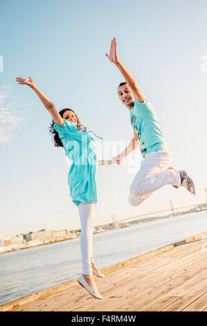 Sweden, Vastra Gotaland, Gothenburg, Couple jumping by river - Stock Photo
