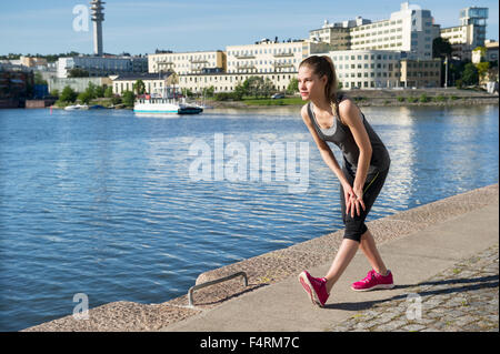 Young woman with water bottle, Hammarby Sjostad, Stockholm, Sweden in background - Stock Photo