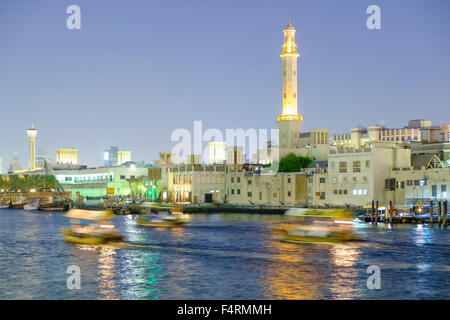 Night view of abra water taxis on The Creek in Deira in old Dubai united Arab Emirates - Stock Photo