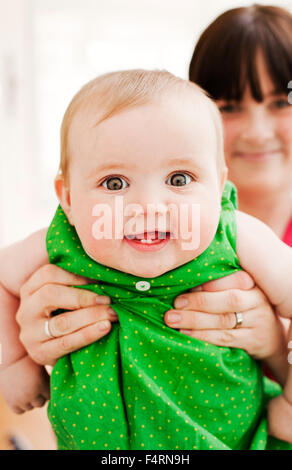 mother showing off her baby girl (18-23 months) - Stock Photo