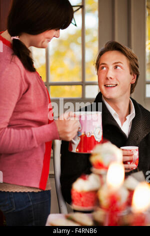 Woman offering mulled wine to man - Stock Photo