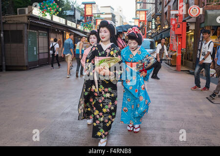Three Geisha walking on Dempoin Street to engagement in Asakusa district of Tokyo Japan - Stock Photo
