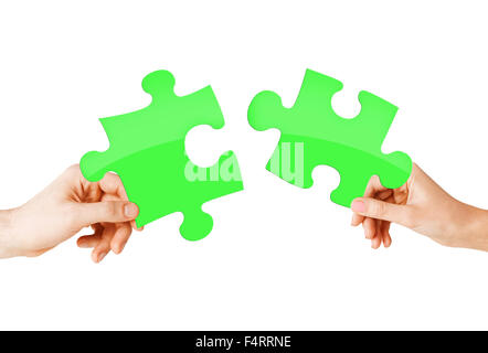 close up of couple hands with green puzzle pieces