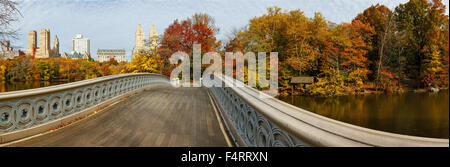 Panoramic of Central Park autumn trees from the Bow Bridge with view of Manhattan Upper West Side buildings. Fall - Stock Photo