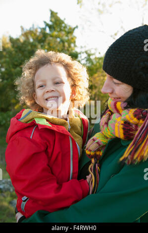 Sweden, Vastra Gotaland, Gothenburg, Mother and daughter (2-3) laughing in field - Stock Photo