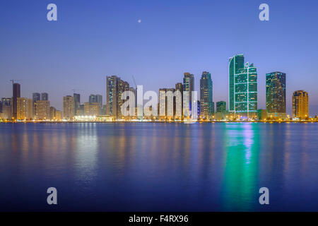 Evening skyline view of modern high-rise apartment buildings on Corniche in Sharjah United Arab Emirates - Stock Photo