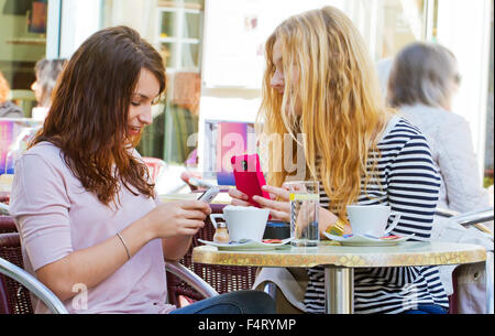 Two young woman with new smart phone - Stock Photo