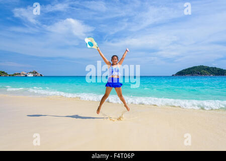 Tourist girl in a blue white striped swimsuit jumping shaped X with happy on the beautiful beach and sea during - Stock Photo