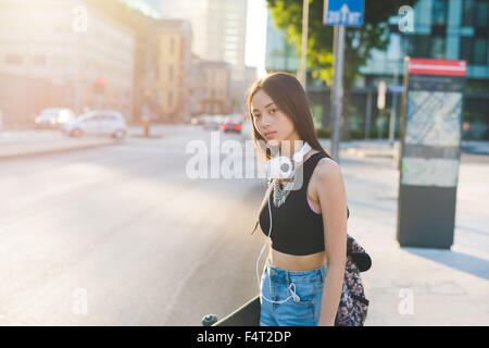 Half length of young handsome asiatic long brown straight hair woman walking outdoor in the city, listening music - Stock Photo