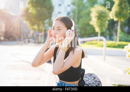 Half length of young handsome asiatic long brown straight hair woman listening music in city backlight with headphones, - Stock Photo