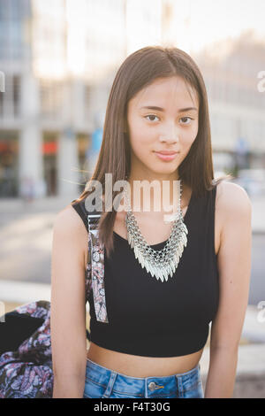 Half length of young handsome asiatic long brown straight hair woman posing in the city, looking in camera, holding - Stock Photo