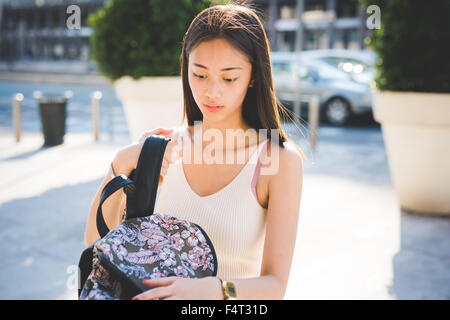 Half length of young handsome asiatic long brown straight hair woman outdoor in the city, searching something in - Stock Photo
