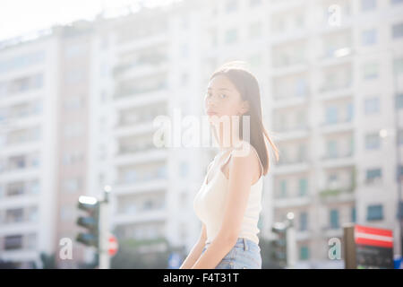 Half length of young handsome asiatic long brown straight hair posing in city backlight, looking in camera, pensive - Stock Photo